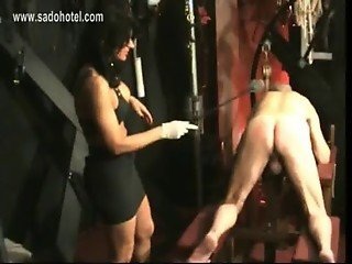 Masked slave got spanked on his ass by horny mistress with big fake tits in a dungeon