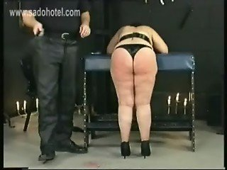 Master tears apart the thights of big slave and hit her on her back with a whip