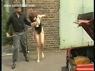 Crying slave with her body covered in candle wax is spanked all over her body in a dungeon