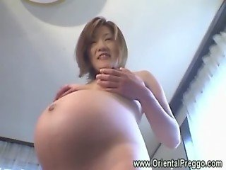 Sexy asian babe shows her preggo belly