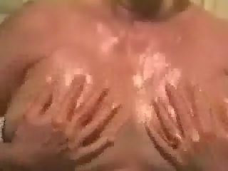 Wife oiling big natural tits for husband