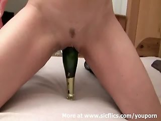 Fucking her cunt with a champagne bottle