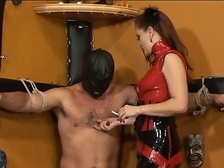 Sexy dominatrix in red dress burns slave with smoking cigarette in dungeon