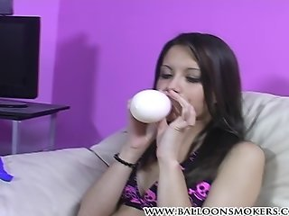 Nikita blowing up balloons and popping them topless
