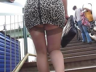 Girl in miniskirt and stockings going upstair