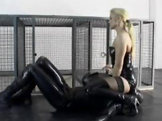 Mistress in latex whipping a slave in full latex